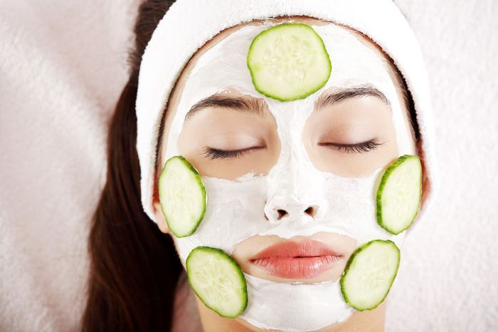 Young woman with cucumber slices on the face in a spa saloon